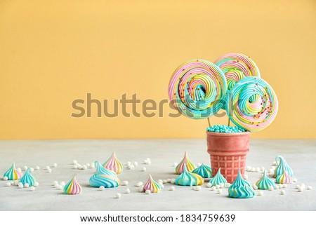 Meringue lollipop on yellow background. Concept of sweet food. Closeup Foto d'archivio ©