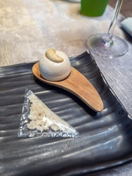 Meringue with cashew nut served with eatable plastic-like bag in fine dining restaurant, selective focus