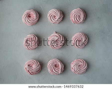 Meringue zephyr marshmallows lined up in a square on a light background. Mortgage the apartment. The view from the top. Pink sweet homemade marshmallow or marshmallow. Colorful meringues on a white #1469337632