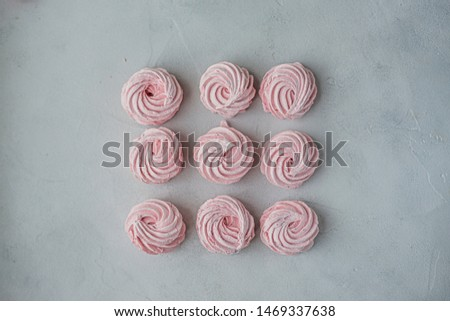 Meringue zephyr marshmallows lined up in a square on a light background. Mortgage the apartment. The view from the top. Pink sweet homemade marshmallow or marshmallow. Colorful meringues on a white #1469337638