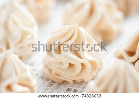 Meringues on white tablecloth, shallow dof.
