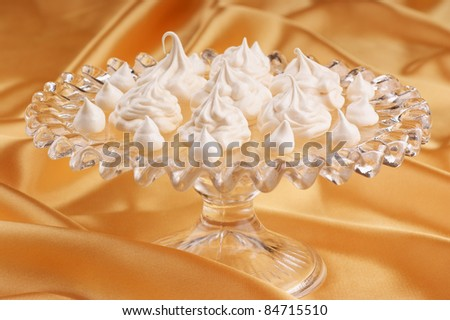Meringues served over a glass cake stand. Selective focus, shallow DOF