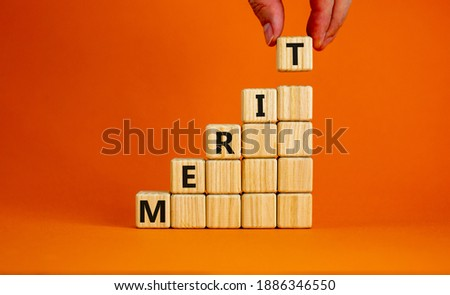 Merit symbol. Wood cubes with word 'merit' stacking as step stair on beautiful orange background, copy space. Male hand. Business and merit concept. Stockfoto ©