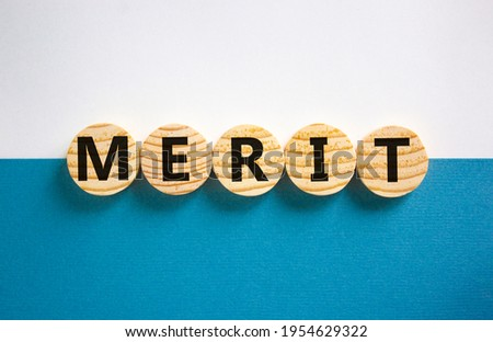 Merit symbol. Wooden circles with the word 'merit'. Beautiful white and blue background, copy space. Business and merit concept. Stockfoto ©