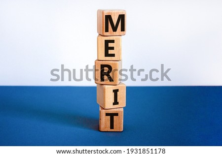 Merit symbol. Wooden cubes with the word 'merit'. Beautiful white and blue background, copy space. Business and merit concept. Stockfoto ©
