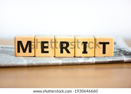 Merit symbol. Wooden cubes with the word 'merit'. Beautiful white background, copy space. Newspaper. Business and merit concept. Stockfoto ©