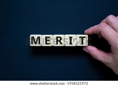 Merit symbol. Wooden cubes with the word 'merit'. Businessman hand. Beautiful black background, copy space. Business and merit concept. Stockfoto ©