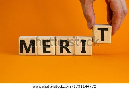 Merit symbol. Wooden cubes with the word 'merit'. Businessman hand. Beautiful orange background, copy space. Business and merit concept. Stockfoto ©