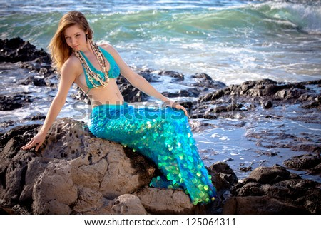 Mermaid in Hawaii with waves crashing around her