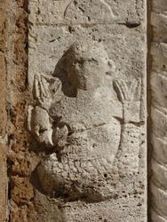 Mermaid sculpture on a church wall. tuscany, italy.