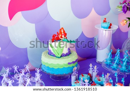 Mermaid theme cake with colorful glitter tails, shells and sea creatures toppers for children's, teen's, novelty birthday and party celebrations.