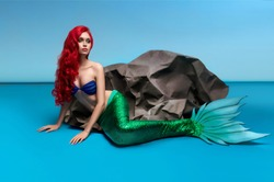 Mermaid with red hair resting near stone on blue background