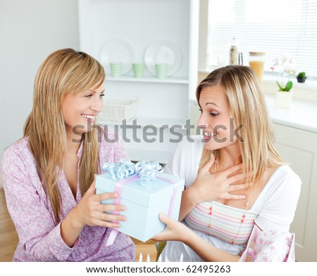 Merry caucasian woman giving a present to her surprised friend for her birthday in the kitchen at home