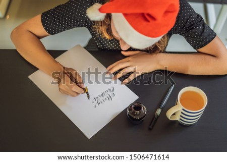 Merry christmas and a happy new year. Calligrapher Young Woman writes phrase on white paper. Inscribing ornamental decorated letters. Calligraphy, graphic design, lettering, handwriting, creation