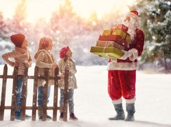 Merry Christmas and Happy Holiday! Cute children girls and boy playing on a winter walk in nature. Happy kids outdoors. Santa Claus presents gifts to nice kids.