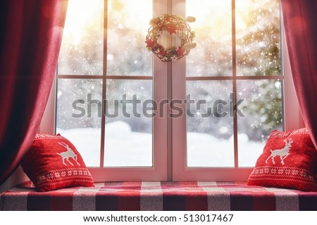 Merry Christmas and Happy Holidays! A beautiful decorated for Christmas window. Winter forest from the window of the house.