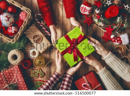 Merry Christmas and Happy Holidays! A mother, father and their daughter prepare Xmas gifts. Baubles, presents, candy with christmas ornaments. Top view. Christmas family traditions. #516500077