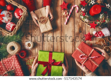 Merry Christmas and Happy Holidays! A mother, father and their daughter prepare Xmas gifts. Baubles, presents, candy with christmas ornaments. Top view. Christmas family traditions. #517143574