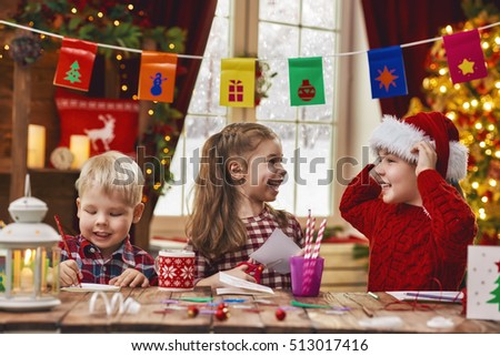 Merry Christmas and Happy Holidays. Adorable little children make cards, gifts and decorations for the holiday. Cute kids are engaged in creativity.
