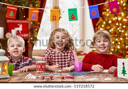 Merry Christmas and Happy Holidays. Adorable little children make cards, gifts and decorations for the holiday. Cute kids are engaged in creativity. #519218572