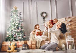 Merry Christmas and Happy Holidays! Cheerful mom and her cute daughters girls exchanging gifts. Parent and two little children having fun and playing together near Christmas tree indoors.