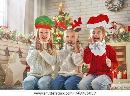 Merry Christmas and Happy Holidays! Children with paper accessories for photo: Santa hat, antlers of a reindeer and the elf headdress. Family party.