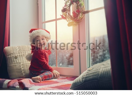 Merry Christmas and happy holidays! Cute little baby girl sitting by the window and looking at the winter forest. Room decorated on Christmas. Kid enjoys the snowfall. #515050003