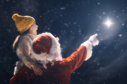 Merry Christmas and happy holidays! Cute little child girl and Santa Claus looking at Christmas star. Christmas legend concept.