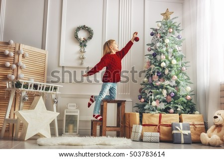 Merry Christmas and Happy Holidays!  Cute little child girl is decorating the Christmas tree indoors. #503783614