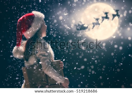 Merry Christmas and happy holidays! Cute little child girl with xmas present. Santa Claus flying in his sleigh against moon sky. Kid enjoy the holiday. Portrait kid with gift on dark background.