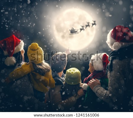 Merry Christmas and happy holidays! Cute little children with mom, dad, grandma and grandpa. Santa Claus flying in his sleigh against moon sky. Family enjoying the holiday on dark background.