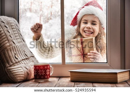 Merry Christmas and happy holidays! Cute little girl looking in window, standing outdoors on winter forest background. Child holding present gift box.