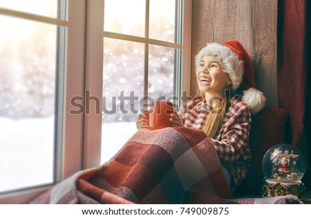 Merry Christmas and happy holidays! Cute little girl sitting by the window with a cup of hot drink and looking at the winter forest. Room decorated. Kid enjoys the snowfall. #749009875