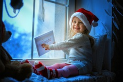 Merry Christmas and happy holidays Cute little girl sitting by the window with a letter to Santa Claus and looking at flying in the sky. Kid sitting in the window at night and waiting for Santa Claus
