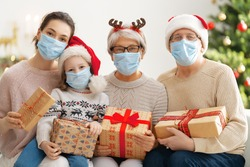 Merry Christmas and Happy Holidays! Grandma, grandpa, mum and children exchanging gifts. Parents and daughters wearing face masks near tree indoors. Loving family with presents in room.
