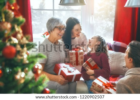 Merry Christmas and Happy Holidays! Grandma, mum, dad and child exchanging gifts. Parents and daughter having fun near tree indoors. Loving family with presents in room. #1220902507