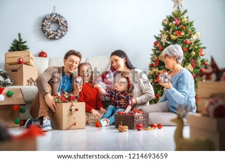 Merry Christmas and Happy Holidays!  Granny, mother, father and children decorate the tree in room. Loving family indoors.