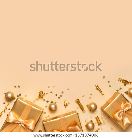 Merry Christmas and Happy Holidays greeting card. Beautiful golden gift balls ribbons confetti stars on gold background top view Flat lay. New Year presents Festive decorations 2020 celebration
