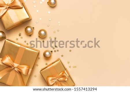 Merry Christmas and Happy Holidays greeting card. Beautiful golden gift with balls and confetti stars on gold background top view Flat lay. New Year presents Festive decorations 2020 celebration