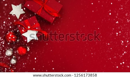 Merry Christmas and Happy Holidays greeting card, frame, banner. New Year. Christmas red handmade gifts, presents on red background top view. Winter holiday theme. Flat lay. #1256173858