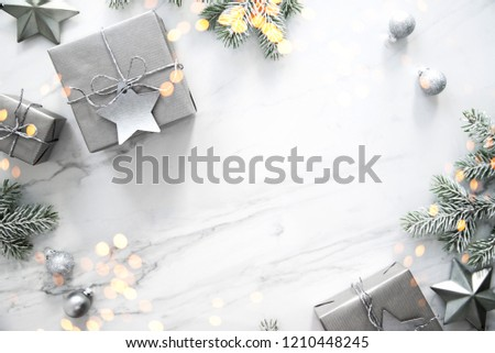 Merry Christmas and Happy Holidays greeting card, frame, banner. New Year. Christmas silver handmade gift boxes on white marble background top view. Winter holiday theme. Flat lay. #1210448245
