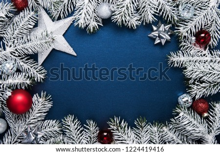 Merry Christmas and Happy Holidays greeting card, frame, banner. New Year. Noel. Christmas ornaments and fir tree on blue background top view. Winter holiday theme. Flat lay. #1224419416