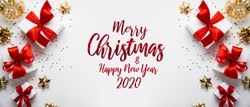 Merry Christmas and Happy Holidays greeting card, frame, banner. New Year. Noel. Christmas gifts and red, golden decor on white background top view. Winter xmas holiday theme. Flat lay