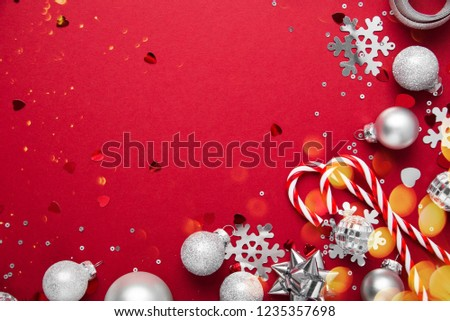 Merry Christmas and Happy Holidays greeting card, frame, banner. New Year. Noel. Christmas white and silver ornaments on red background top view. Winter holiday xmas theme. Flat lay. #1235357698