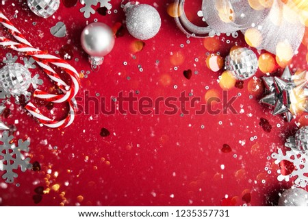 Merry Christmas and Happy Holidays greeting card, frame, banner. New Year. Noel. Christmas white and silver ornaments on red background top view. Winter holiday xmas theme. Flat lay. #1235357731
