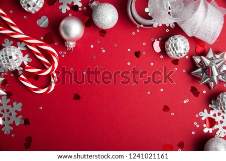 Merry Christmas and Happy Holidays greeting card, frame, banner. New Year. Noel. Christmas white and silver ornaments on red background top view. Winter holiday xmas theme. Flat lay. #1241021161