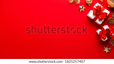 Merry Christmas and Happy Holidays greeting card, frame, banner. New Year. Noel. Christmas white, silver and golden ornaments and gifts on red background top view. Winter xmas holiday theme. Flat lay