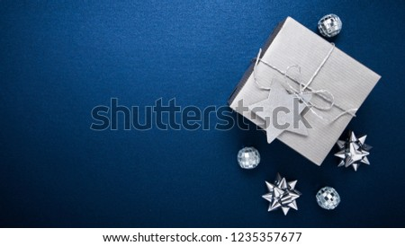 Merry Christmas and Happy Holidays greeting card, frame, banner. New Year. Noel. Silver Christmas gifts, ornaments on blue background top view. Winter holiday xmas theme. Flat lay. #1235357677