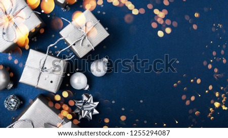Merry Christmas and Happy Holidays greeting card, frame, banner. New Year. Noel. Silver Christmas gifts, ornaments on blue background top view. Winter holiday xmas theme. Flat lay. #1255294087