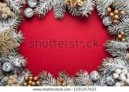 Merry Christmas and Happy Holidays greeting card, frame, banner. New Year. Noel. Silver, white and red Christmas ornaments and fir tree on red background top view. Winter holiday xmas theme.